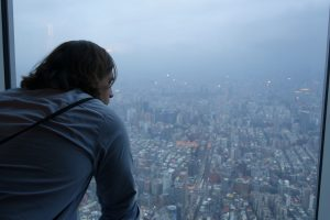 William Bork '11 looking out window over Taipei, Taiwan.