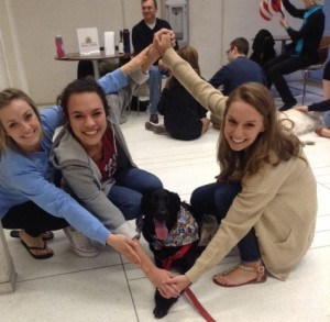photo of three students with a therapy dog